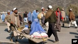 Des familles afghanes traversant la frontière pakistano-afghane à Turkham, le 30 janvier 2007.