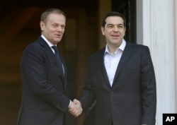 Greece's Prime Minister Alexis Tsipras, right, poses with European Council President Donald Tusk for a photo before their meeting at Maximos Mansion in Athens, March 3, 2016.