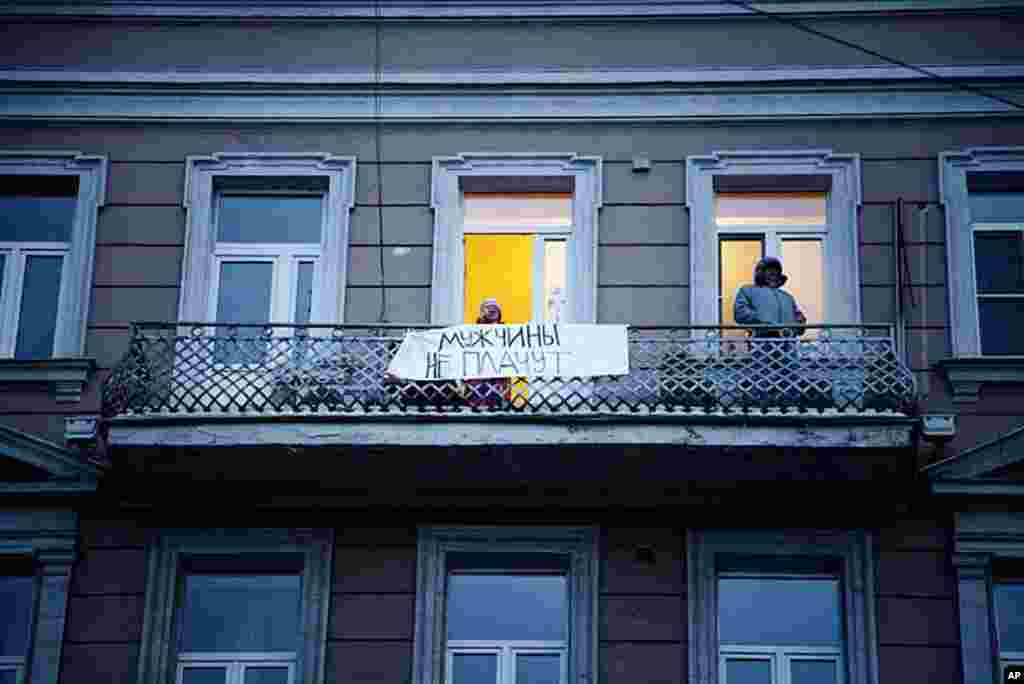 "A sign hangs from an apartment balcony reads, ""Men don't cry."" On Sunday evening, Vladimir Putin spoke to a large crowd of supporters and appeared to tear up on camera, March 5, 2012, (VOA - Y. Weeks)."