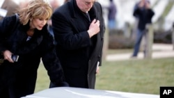 Diana Rambo and her husband pause at a casket of unidentified remains after services to honor two sailors from the USS Monitor, at Arlington National Cemetery, March 8, 2013 in Arlington. Mrs. Rambo is related to USS Monitor crew member Jacob Nicklis.