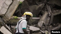 Un pompier parmi les décombres après qu'un immeuble de deux étages se soit effondré dans le district d'Utako, à Abuja, le 18 octobre 2013.