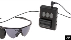 This undated product image provided by Second Sight Medical Products shows a small video camera and transmitter mounted on a pair of glasses. Images from the camera are processed into electronic data that is wirelessly transmitted to electrodes implanted