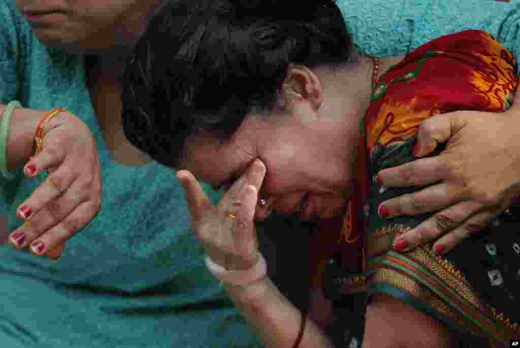 The wife of Laxman Neupane, one of the police officers killed in clashes in western Nepal, mourns after his body was brought to Kathmandu. Ethnic protesters, demanding statehood, attacked police with spears and knives in Tikapur, 400 kilometers (250 miles) west of the capital.