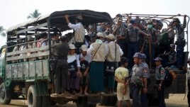 FILE - Volunteers and police board vehicles before proceeding to Rohingya refugee camps to collect data for the census in Sittwe, March 31, 2014.