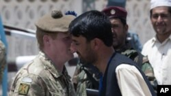 A British army officer (L) receives flowers from an Afghan man during a ceremony to hand over control of security in Lashkar Gah in Helmand province, southern Afghanistan, July 20, 2011.