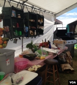 Festival fan Tim, a onetime professional cook, has a full kitchen at his campsite. (VOA/K. Cole)
