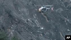 Sebuah helikopter terbang di atas reruntuhan pesawat penumpang Germanwings yang hancur di sebuah sisi gunung dekat pegunungan Alpen, Perancis, 24 Maret 2015 (AP Photo/Claude Paris)