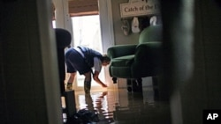 Sherry Rose measures the water level in her home as floodwaters slowly rise in Holly Grove, Arkansas, May 10, 2011