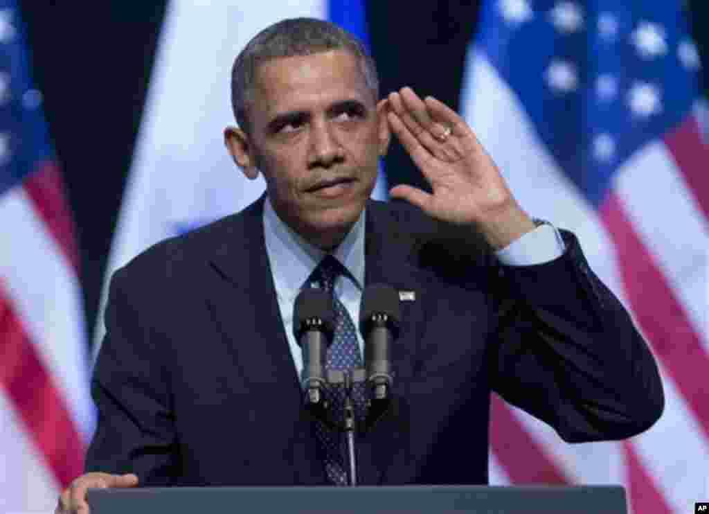 21일 예루살렘 국제컨벤션센터에서 강연하던 중 자신을 향해 소리치는 청중에 귀를 대는 오바마 대통령.