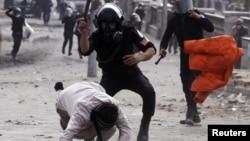 Polisi anti huru-hara Mesir memukul seorang demonstran anti pemerintah dalam bentrokan di Kairo, Senin (28/1).