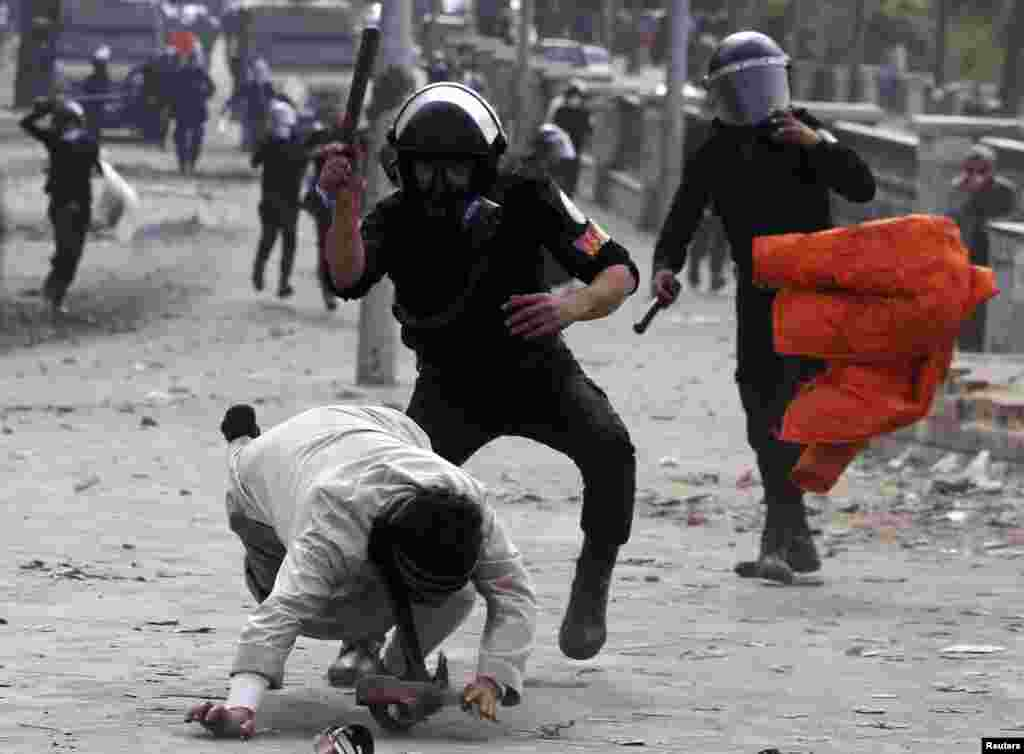 Riot policemen beat a protester opposing Egyptian President Mohamed Morsi, during clashes along Qasr Al Nil bridge, which leads to Tahrir Square in Cairo.