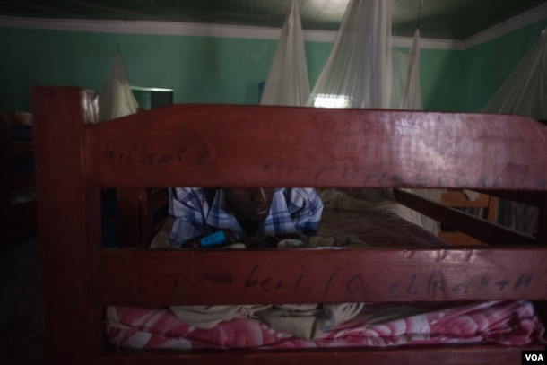 A former Al Shabab member texts on his phone while lying on his bed in a dormitory at a rehabilitation center for former militants in Baidoa, Somalia, Sept. 17, 2016. (Photo: J. Patinkin/VOA)