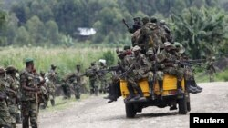 Des rebelles du M23 à bord d'un camion alors qu'ils se préparaient à se retirer de Sake, à 42 kilomètres à l'ouest de Goma, dans l'est du Congo - novembre 30, 2012.