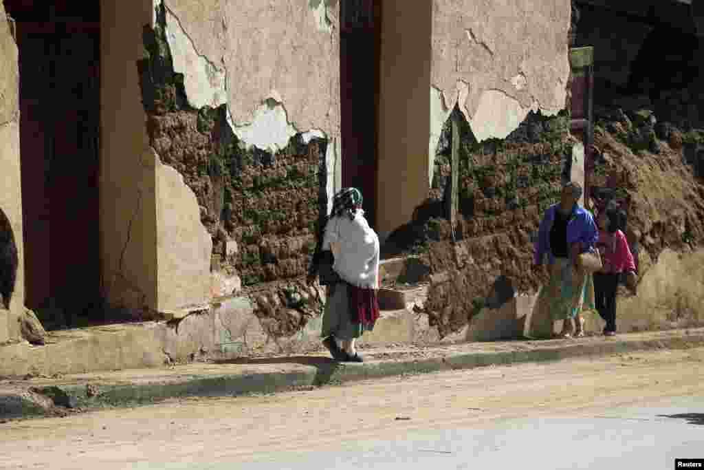 8일 지진으로 무너진 과테말라 산마르코스의 건물 앞을 지나는 주민.
