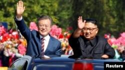 South Korean President Moon Jae-in and North Korean leader Kim Jong Un wave during a car parade in Pyongyang, North Korea, Sept. 18, 2018.