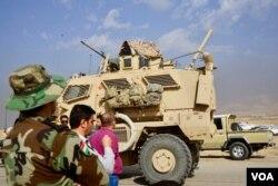 Local Christians and Kurdish peshmerga fighters watch as Iraqi armor trundles past them, in Bartilla, Iraq, Oct. 31, 2016. (J. Dettmer/VOA)