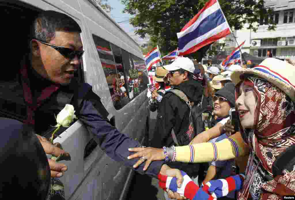 Anti-government protesters give flowers to a Thai border policeman as he leaves the Government House following an agreement between the army and protesters, Bangkok, Thailand, Jan. 19, 2014.