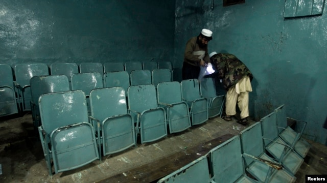 Security officials collect evidence at a movie theater, the site of explosions, in Peshawar, Feb. 2, 2014.