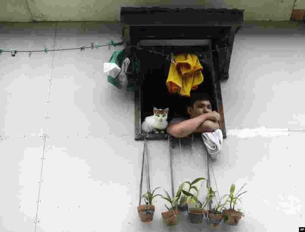 필리핀 마닐라 동쪽 산 후안시 마을에서 태풍 산바의 영향으로 홍수가 발생한 가운데 자신의 위층 창에서 고립된 한 남자