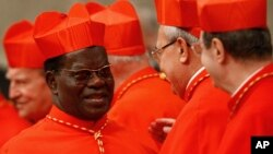Cardinal Laurent Monsengw, of the Democratic Republic of Congo, left, is congratulated by other cardinals after being elevated by Pope Benedict XVI during a consistory inside St. Peter's Basilica, at the Vatican, Nov. 20, 2010.