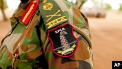 FILE - A Sudan People's Liberation Army (SPLA) commander dons his division's insignia in Bentiu, Unity State, South Sudan, May 11, 2012. A number of SPLA commanders are among officials on the U.N. sanctions list.