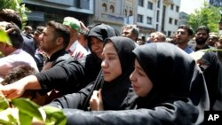 FILE - Iranians attend the funeral of victims of an Islamic State militant attack, in Tehran, Iran, June 9, 2017. Attacks claimed by Islamic State killed 17 people.