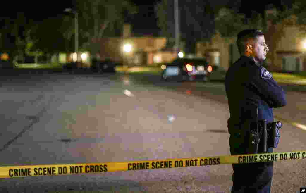 A police officer stands guard inside an area roped off with crime scene tape near a home being investigated by police on Dec. 3, 2015, in Redlands, California.
