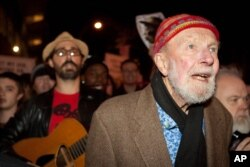 FILE - Activist musician Pete Seeger, 92, left, marches with nearly a thousand demonstrators sympathetic to the Occupy Wall Street protests for a brief acoustic concert in Columbus Circle in New York, Oct. 21, 2011.