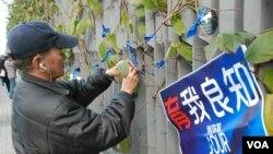 參與反滅聲遊行集會人士在特首辦公室外繫上象徵新聞自由的藍絲帶 (美國之音湯惠芸拍攝)