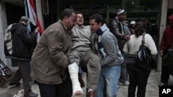Anti-government demonstrators carry a man wounded during clashes with pro-government protesters, at a makeshift medical triage station, near Tahrir square, the center of anti-government demonstrations, in Cairo, Egypt, Wednesday, Feb. 2, 2011. Thousands o