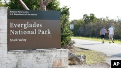 Visitors walk past a sign for Everglades National Park as they enter from overflow parking, Jan. 2, 2019, in Everglades National Park, Fla. Human feces, overflowing garbage, illegal off-roading and other damaging behavior were beginning to to overwhelm some of the national parks, as a partial government shutdown drags on.