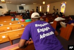 A man listens as Black Voters Matter co-founder LaTosha Brown speaks at a church as part of The South Is Rising Tour 2018 on Aug. 22, 2018, in Warner Robins, Ga.
