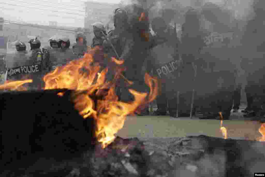 Police stand guard near tyres set on fire by activists of Bangladesh Nationalist Party (BNP) during a nationwide blockade in Dhaka December 9, 2012. Police fired rubber bullets and tear gas to disperse protesters staging blockades across Bangladesh on Sun