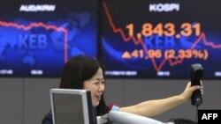 Một nhà giao dịch tiền tệ ở Nam Triều Tiên vui mừng trước màn hình hiển thị chỉ số giá chứng khoán tại trụ sở Ngân hàng Nam Triều Tiên ở Seoul, ngày 10/8/2011
