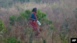 Seorang perempuan India berjalan di sebuah tanah lapang setelah buang air buka di lapangan terbuka pada Hari Toilet Sedunia di pinggiran Jammu, India, 19 November 2014.