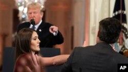 Presiden Donald Trump menunjuk ke wartawan CNN, Jim Acosta, sedangkan seorang staf Gedung Putih mengambil mikrofon dari tangan