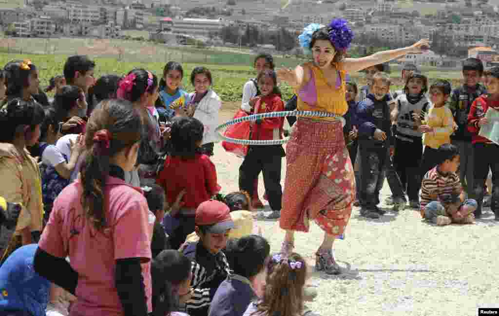 Members of Clowns Without Borders entertain Syrian refugee children in Jab Janine, West Bekaa, Lebanon, June 2, 2014. Clowns Without Borders is an international non-profit organization that uses laughter to relieve suffering among children in refugee camps, conflict zones and natural disaster areas.