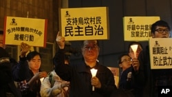 "A protester, center, holds up a placard reading: ""Supporting Wukan villagers, democracy autonomy"" during a candlelight vigil outside the China Liaison Office in Hong Kong to support the Wukan villagers, December 20, 2011."