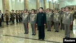Pemimpin Korea Utara Kim Jong Un (tengah) berdiri memberi penghormatan di depan patung-patung mendiang pendahulunya di Istana Kumsusan di Pyongyang.