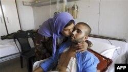 Binh sĩ Syria bị thương được mẹ chăm sóc trong bệnh viện quân sự Teshrin ở Damascus