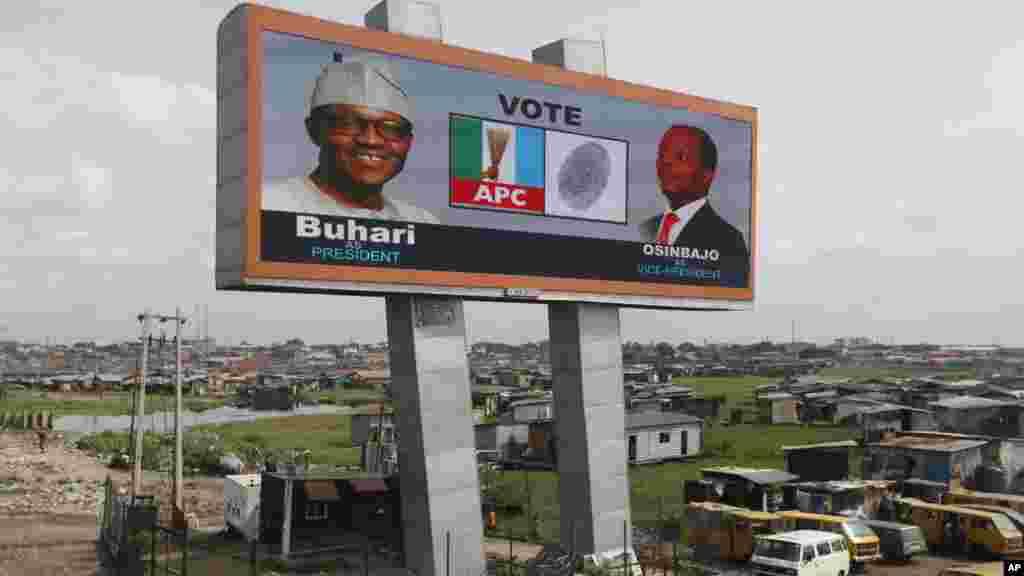 Un panneau d'affichage électronique du candidat de l'opposition présidentielle, Muhammadu Buhari, du parti tous les progressistes Congrès et son colistier, Yemi Osinbanjo est apperçu dans un bidonville de Lagos, au Nigeria, mardi 24 mars2015.