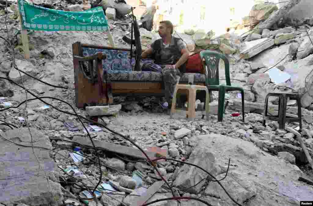 A Free Syrian Army fighter sits on a sofa along a street in Aleppo's Salaheddine neighborhood, July 31, 2013