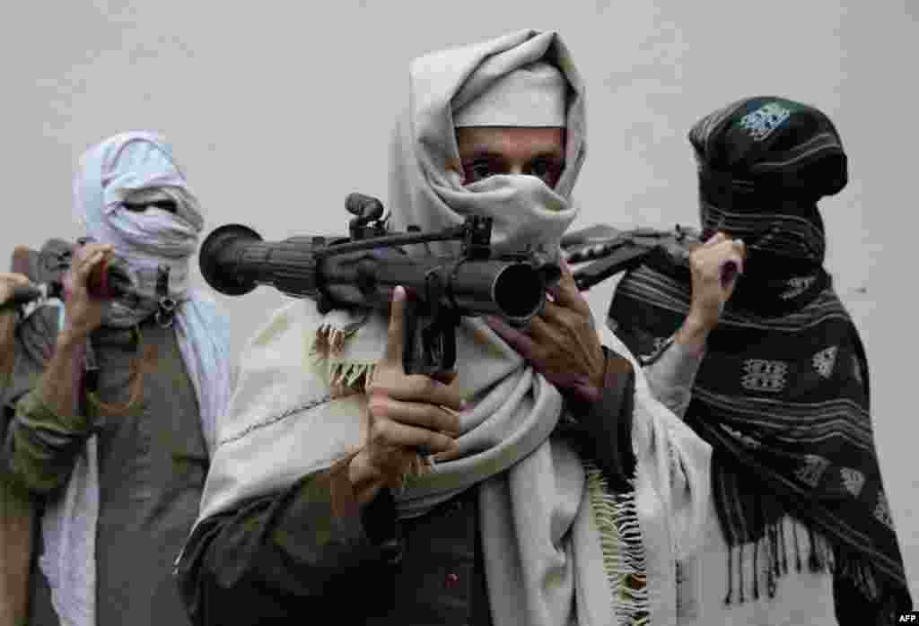 Former Afghan Taliban fighters carry their weapons before handing them over as part of a government peace and reconciliation process at a ceremony in Jalalabad. More than a dozen former Taliban fighters from Ghani district of Nangarhar province handed over their weapons as part of the program.