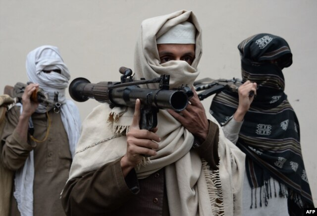 Former Afghan Taliban fighters carry their weapons before handing them over as part of a government peace and reconciliation process at a ceremony in Jalalabad, Jan. 12, 2016.