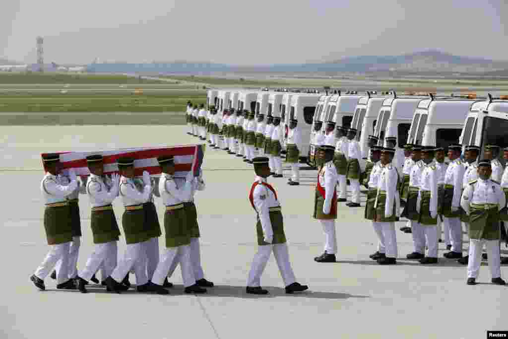 The remains of a passenger of the downed Malaysia Airlines MH17 is carried to a hearse, at the Bunga Raya complex of KLIA airport, in Sepang, Malaysia, Aug. 22, 2014.