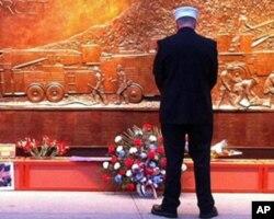 一名消防仪仗队员在世贸中心旧址附近的遇难消防队员纪念墙前静思
