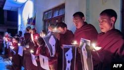 Các tăng sĩ Tây Tạng cầm ảnh của những người Tây Tạng bị lực lượng Trung Quốc bắn chết, trong một buổi đốt nến cầu nguyện ở Dharamsala, Ấn Độ, 25/1/12