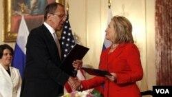 Menlu AS Hillary Clinton berjabat tangan dengan Menlu Rusia Sergey Lavrov setelah penandatanganan kerjasama bilateral di Washington (13/7).