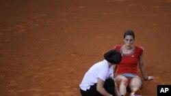 Petugas paramedis memeriksa kaki kanan Andrea Petkovic yang terkilir dalam pertandingan Grand Prix di Stuttgart, Kamis (26/4).