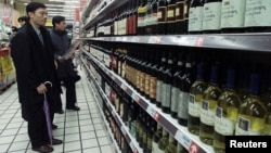 Chinese shoppers look at rows of wine at a supermarket in Shanghai. (Mar 2002 file photo)